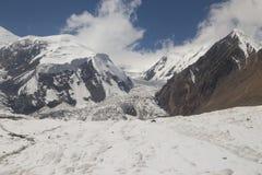 Glaciär på en bakgrund av berg och blå himmel Fotografering för Bildbyråer