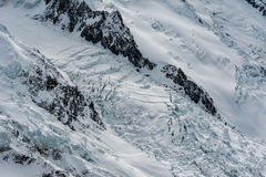 Glaciärdes Bossons som flödar ner mellan bergkanter i wint Royaltyfri Bild