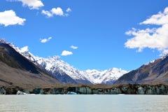 Glaciären på en sjö på foten av snö täckte berg Royaltyfri Fotografi