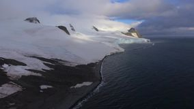 Glaciären täcker den mörka stranden av Antarktis Andreev stock video