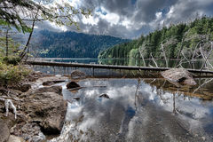Glacial Black Lake surrounded by the forest Royalty Free Stock Photography