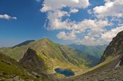 Glacial Caltun lake from Fagaras Mountains. Glacial lake Caltun from Fagaras Mountains, Romania. Beautiful blue sky with white fluffy clouds royalty free stock images