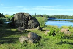 Glacial erratic boulders over the lake Stock Photo