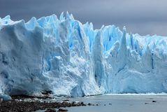 Glacial ice Perito Moreno Glacier from Argentino Lake - Argentina. Light blue glacial ice field Perito Moreno Glacier with dark clouds seen from Argentino Lake Stock Photo