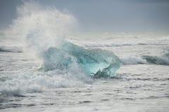 Glacial Iceberg in Beach Surf. Stock Photo