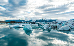 Glacial lagoon in Iceland, cloudy weather, mountains on the horizon. The glacial lake reflects the sky Royalty Free Stock Photo