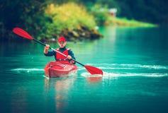 Glacial Lake Kayak Trip. Caucasian Tourist Paddling in the Red Kayak royalty free stock photo