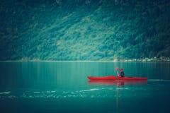 Glacial Lake Kayaking. Caucasian Sportsman Paddling in the Red Kayak stock photos