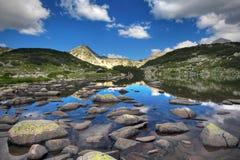 Glacial lake and rocks. Glacial lake Zabecko with Hvoinat peak at national park Pirin, Bulgaria royalty free stock images