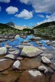 Glacial lake and rocks. Glacial lake Zabecko with Hvoinat peak at national park Pirin, Bulgaria stock photography