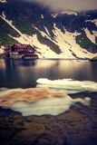 A glacial lake with some ice cap on it set high above in the mou. Ntains before the snow melted completly with a house on the shore in Romania stock photo