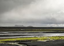 Glacial river in black sand desert with bright green moss vegetation in Highlands of Iceland, Europe stock images