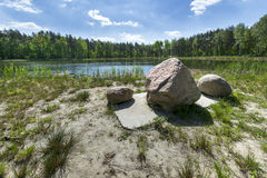 Glacial stones on the forest lake Royalty Free Stock Photos