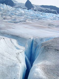 Glacial stream and crevasse. A glacial stream waterfalls into a deep crevasse on Mendenhall Glacier in Juneau, Alaska stock photo