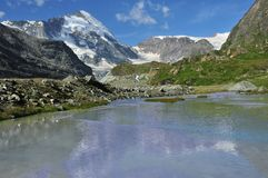Glacial Stream and Dent d'Herens. A meltwater stream running beside a lateral moraine in the Zmutt valley of the Swiss Alps. In the background the Dent d'Herens Stock Images