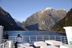 Glacial valley. MILFORD SOUND, JULY 8, 2009: Tourists enjoy the view of Milford Sound, Fiordland, New Zealand, from teh stern of a tourist launch Royalty Free Stock Photo