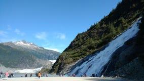 Glaciar de Mendenhall en Juneau Alaska Glaciar grande que resbala dentro de un lago con una cascada al lado de ella Parada turíst imagen de archivo