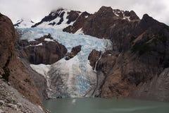 Glaciar que fluye abajo de las montañas en el lago Fotografía de archivo