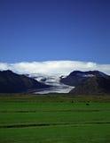 Glaciar y campos verdes Fotografía de archivo libre de regalías