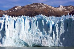 Glacier against mountain. Patagonian glacier in lake argentina with the andes mountains as the backdrop stock images