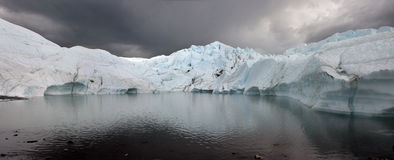 Glacier in Alaska. View of a glacier ending in the water under a see of dark clouds Stock Images