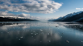 Glacier Bay Alaska. Glass-like surface dotted with floating ice. Blue water and sky, white clouds, snow capped mountains. Calm, sunny, cold Stock Photography