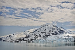 Glacier Bay Ice and Snow, Alaska. Glacier, ice,  and snow capped mountains under a bold, billowy, cloudy sky, in Glacier Bay National Park, Alaska in the inside Stock Photography