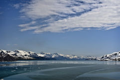 Glacier Bay National Park, Alaska. Panoramic view of snow capped mountains and water under a blue sky with clouds, in Glacier Bay National Park, Alaska Stock Photography