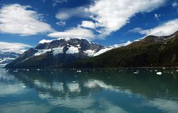 Glacier Bay Reflecting Clouds. Glacier Bay, Alaska with puffy cumulus clouds and glaciers running through mountains, reflecting off the water Royalty Free Stock Photo