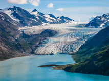 Mountain range and glacier. Scenic view of a snow capped mountain range and glacier with blue sea or lake in the foreground Stock Photos