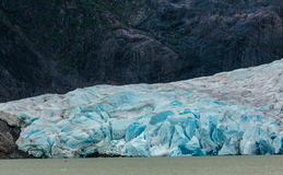 Glacier Blue Ice. Juneau, AK, USA - May 25, 2016: Kayakers are dwarfed as they approach to view moraine of the Mendenhall Glacier stock photos