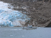 Glacier Boat Ride. A boat travels in front of a glacier in Alaska Stock Photo