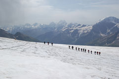 Glacier conquest by alpinists. A group of climbers moving through the glacier Royalty Free Stock Images