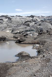 Glacier covered with black volcanic ash - Iceland Stock Photo
