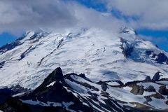 Glacier with crevasses on mountain top and clouds. Stock Images