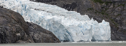 Glacier Fall. Pure white and blue ice flows between rock walls to the lake Royalty Free Stock Photos