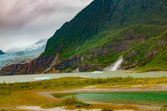 Glacier and Falls. Juneau, AK, USA - May 25, 2016: Panorama of the moraine and blue ice of the Mendenhall Glacier, Mendenhall Lake, Nugget Falls and floating stock images