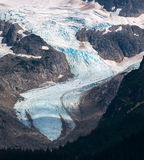 Glacier flowing down mountain valley Royalty Free Stock Images