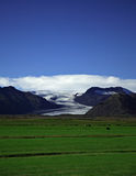 Glacier and green fields. Against a blue sky Iceland Royalty Free Stock Photography