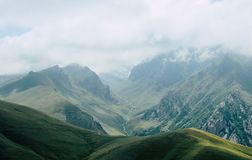 Glacier in a green Valley and clouds in the mountain. Fog in the mountains of Armenia with a glacier in a green valley royalty free stock image