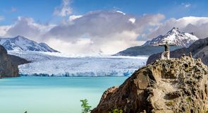 Man hiking with glaciers and lake and mountains in distance stock photography