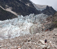Glacier and hiker on moraine Royalty Free Stock Photo