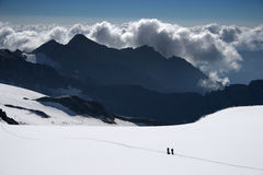 Glacier hiking. Glacier tourist with dark clouds in the background royalty free stock photo