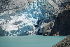 Glacier icefall into the lake. Mountain glaciers landscape. High peaks covered with blue ice and white snow. Huge ice blocks falling in Patagonia. Icefalls Royalty Free Stock Image
