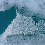 Glacier Lagoon with icebergs from above. Aerial View. Cracked Ice from drone view. Background texture concept royalty free stock photos