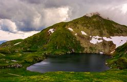 Glacier lake Capra at the foot of the mountain. Lovely summer scenery on a cloudy day. popular travel destination in Southern Carpathian mountains of Romania Royalty Free Stock Photos