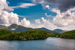 Glacier lake Capra in Southern Carpathians. Beautiful summer landscape with gorgeous sky in Fagaras Mountains of Romania Royalty Free Stock Photography
