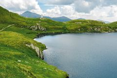 Glacier mountain lake in summer. Beautiful nature scenery in romania. wonderful background with water, grass, and rocks. location fagaras ridge royalty free stock photography