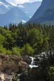 Glacier Nationalpark-Wasserfall mit Bergen Lizenzfreie Stockfotografie