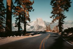 Glacier Point Road with Half Dome, Yosemite National Park, California, USA. Beautiful view of winding Glacier Point Road with famous Half Dome summit in golden royalty free stock photos